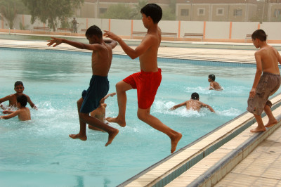 Iraqi children jump into the Al Jadida Public Swimming Pool after its ribbon-cutting ceremony in the Al Jadida district of Baghdad, Iraq, June 7, 2008. DoD photo by Staff Sgt. Brian D. Lehnhardt, U.S. Army. (Released